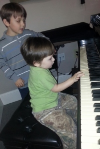 Middle Boy helping Littlest at the church's piano