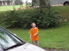 Middle Boy catching rain drops