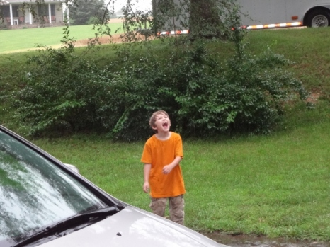 Middle Boy catching rain drops