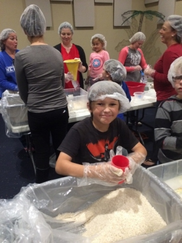Middle Boy preparing meals for people in Haiti