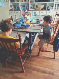 Middle Boy helping Littlest with math on my sick day.